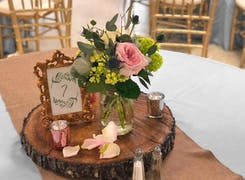 A lush table centerpiece, surrounded by candles and rose petals
